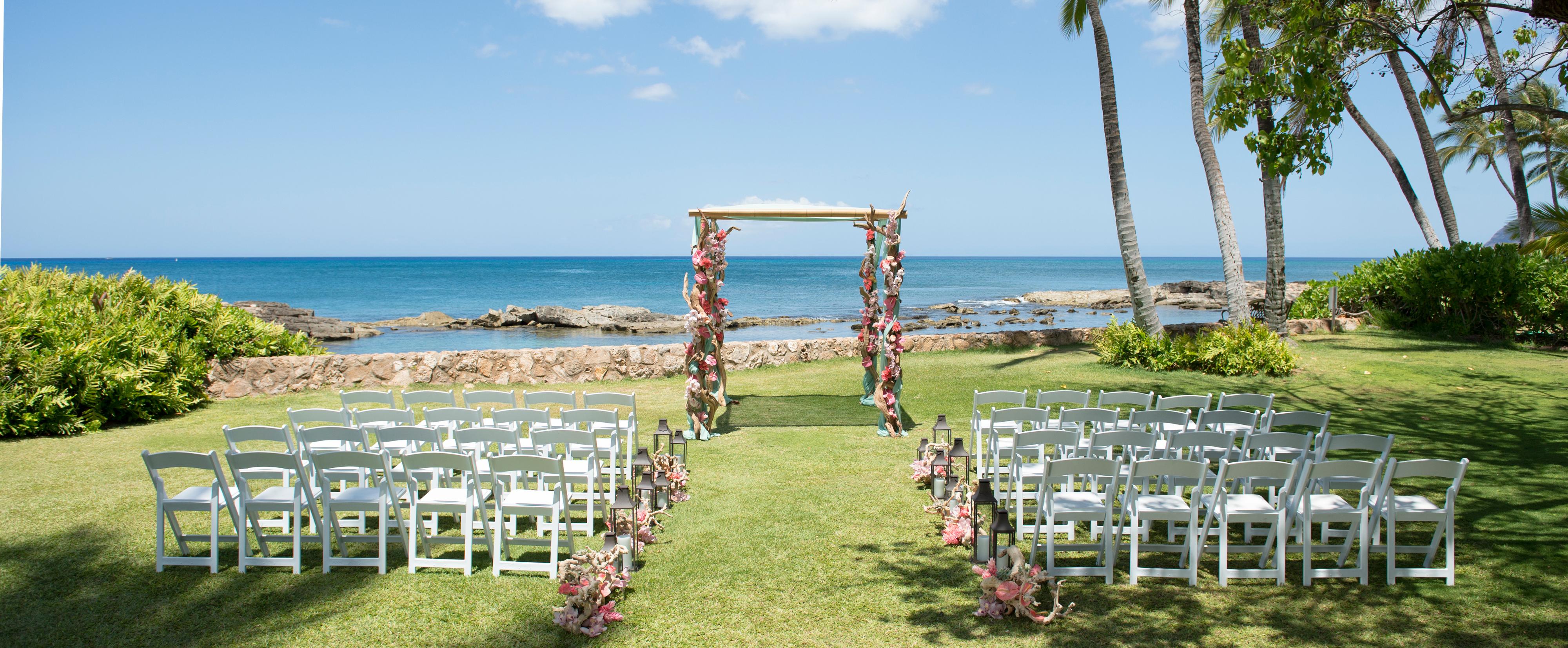 海を見下ろす祭壇につながる芝生の通路に並べられたホワイトチェア