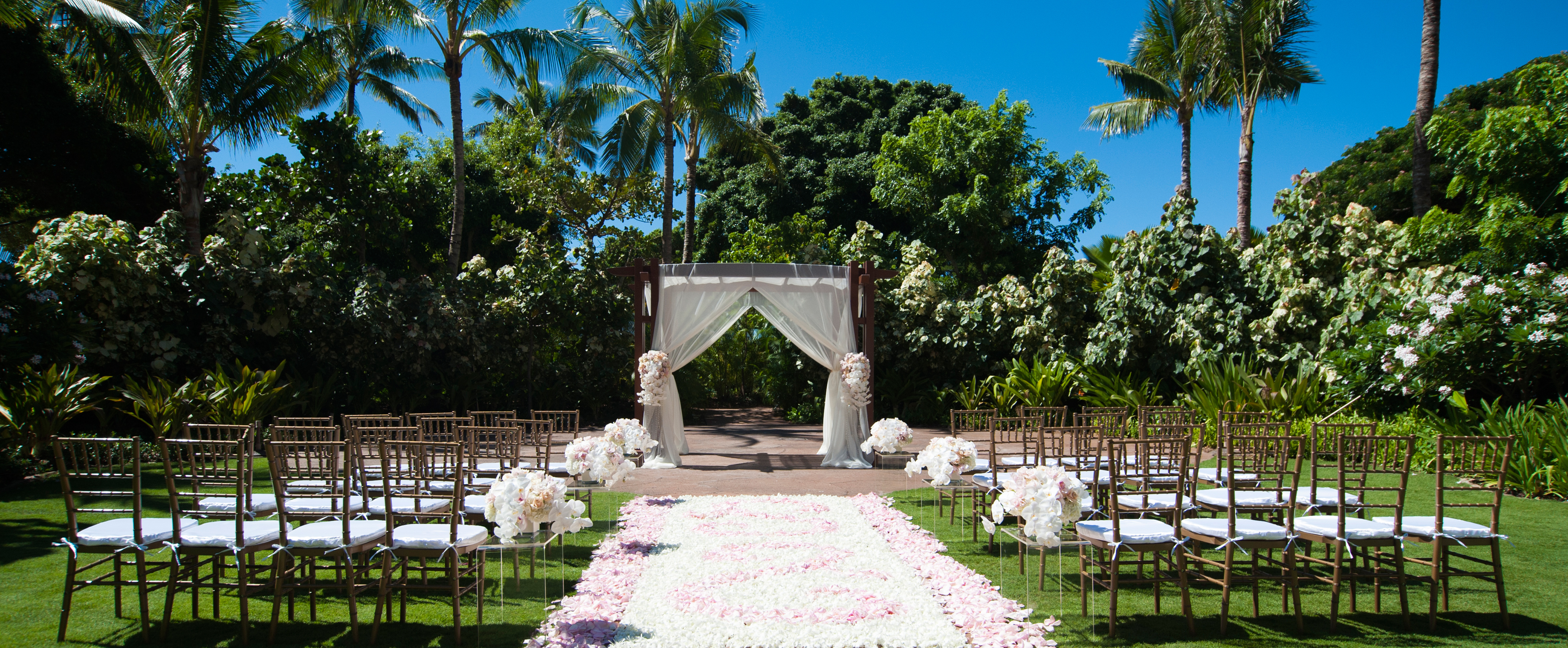 Rows Of Chiavari Chairs Line A Rose Petal Aisle Leading To White Draped Altar