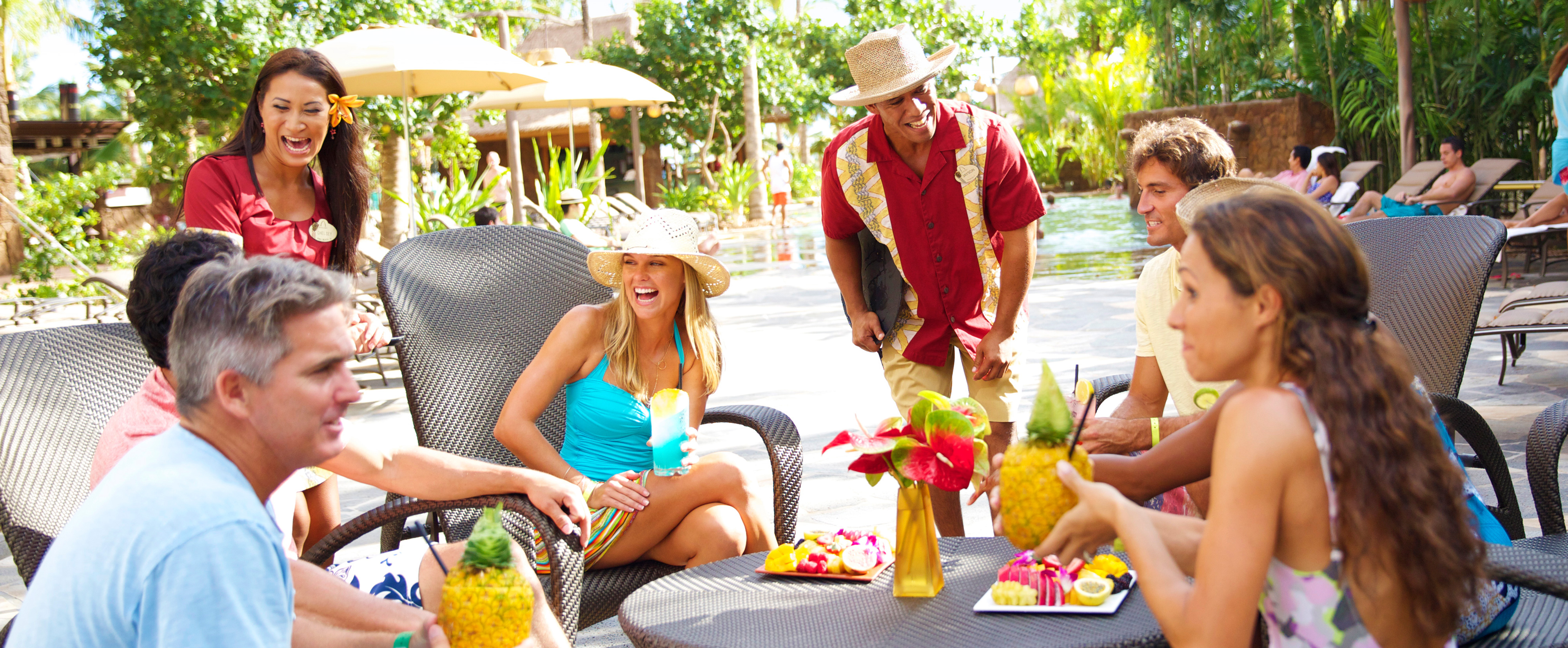 Two servers tend to 3 couples enjoying pineapple drinks and tropical fruit plates at a table near a pool