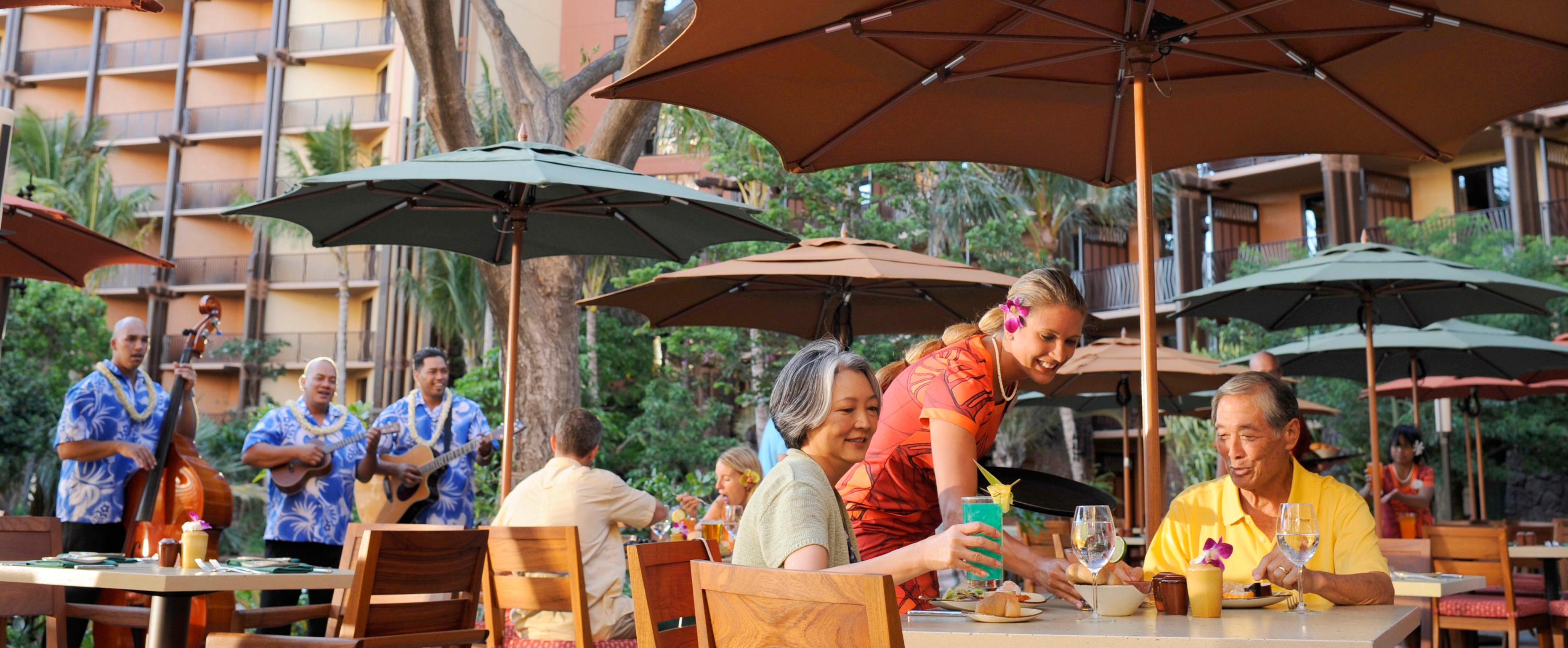 ハワイアン・ミュージシャンのトリオが音楽を奏でる間、高齢カップルのテーブルにパンのバスケットをセットするウェイター・ウェイトレス。