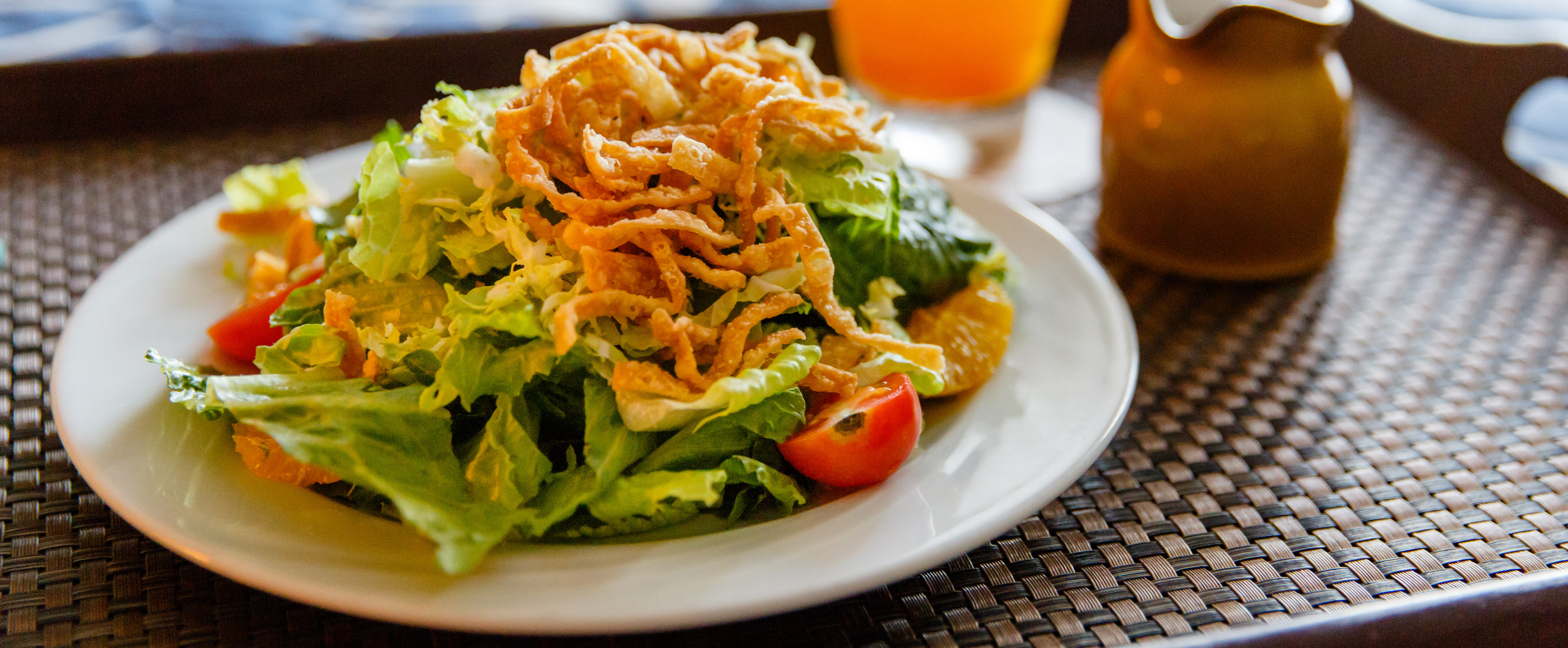A plate of Asian-inspired salad topped with crispy noodles on a wicker serving tray with a beverage