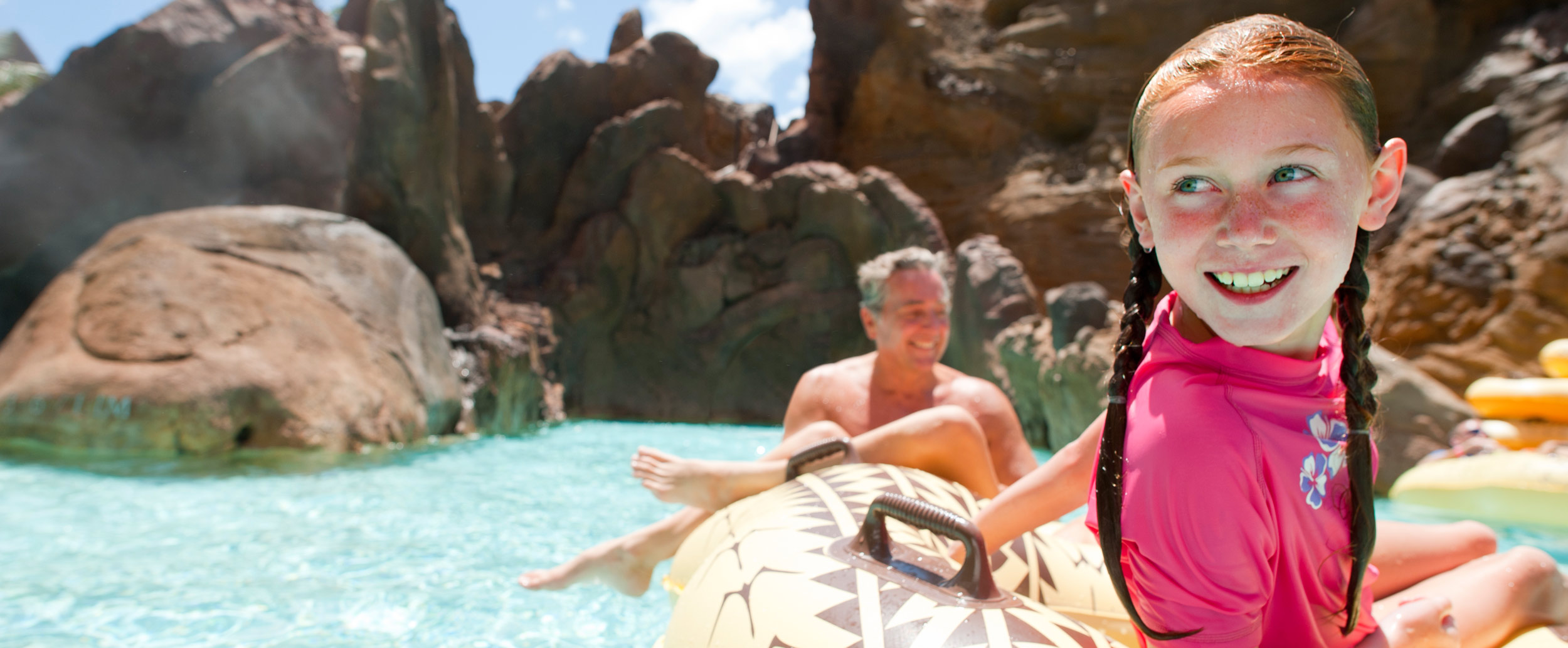 A little girl smiles, riding an inner tube on a lazy river with her dad in the background