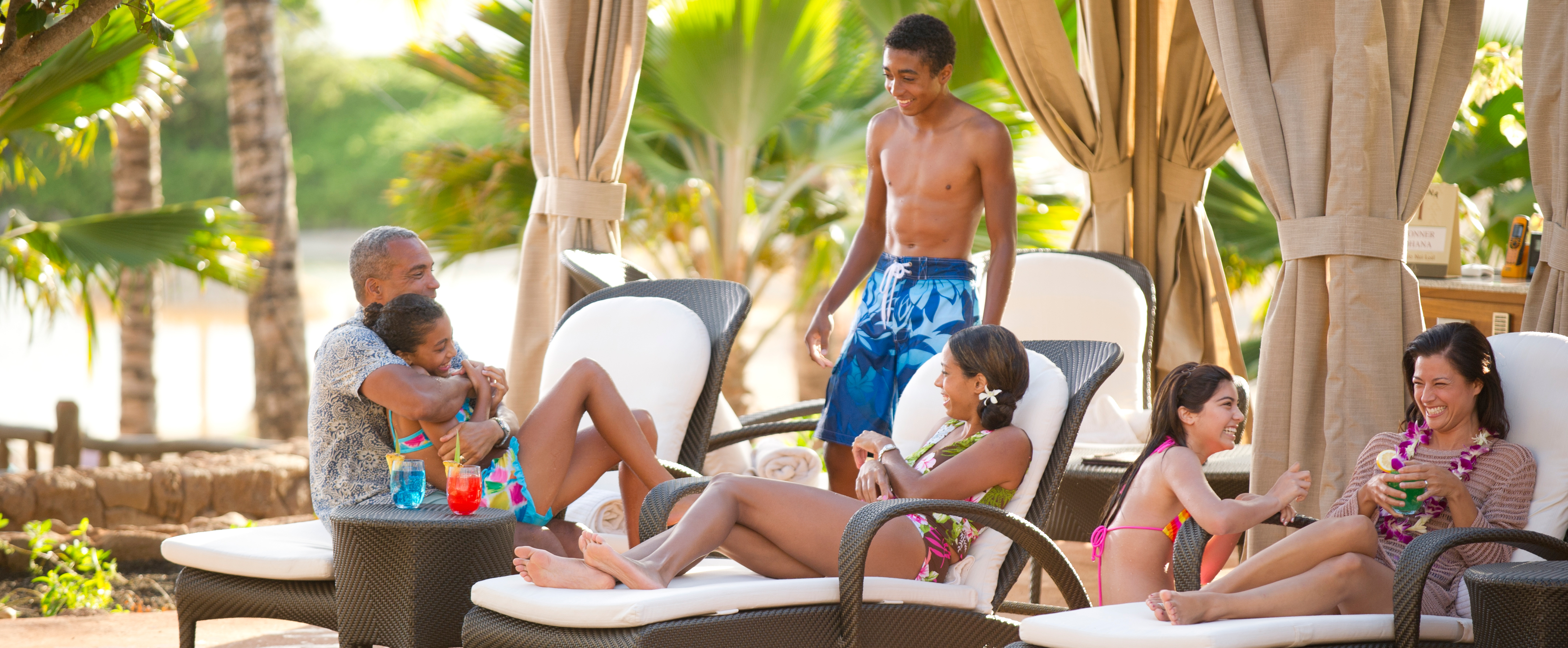 A family relaxes under a poolside cabana at Aulani