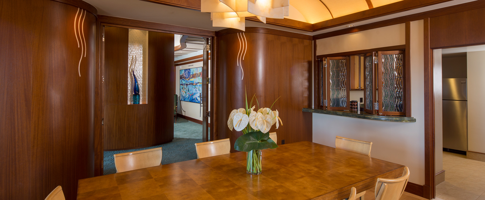 A wood paneled dining room features a long table and chairs and a ceiling lighting fixture
