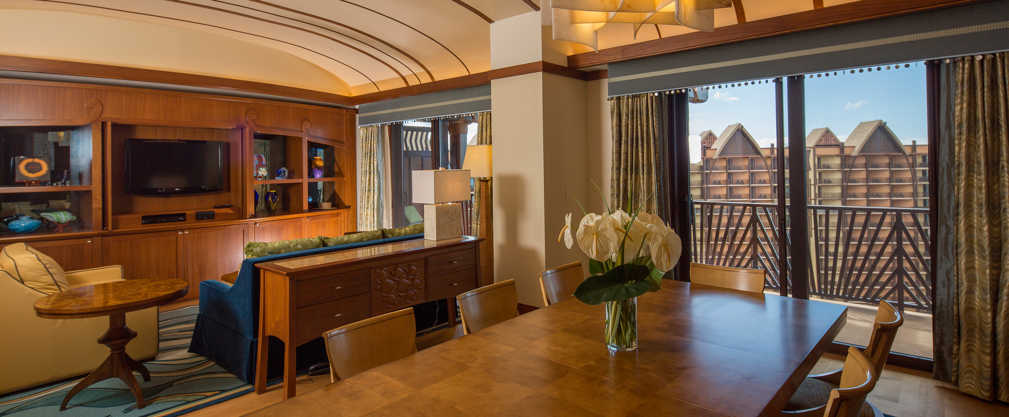 The living area of the suite includes an entertainment center, plush seating and the dining area