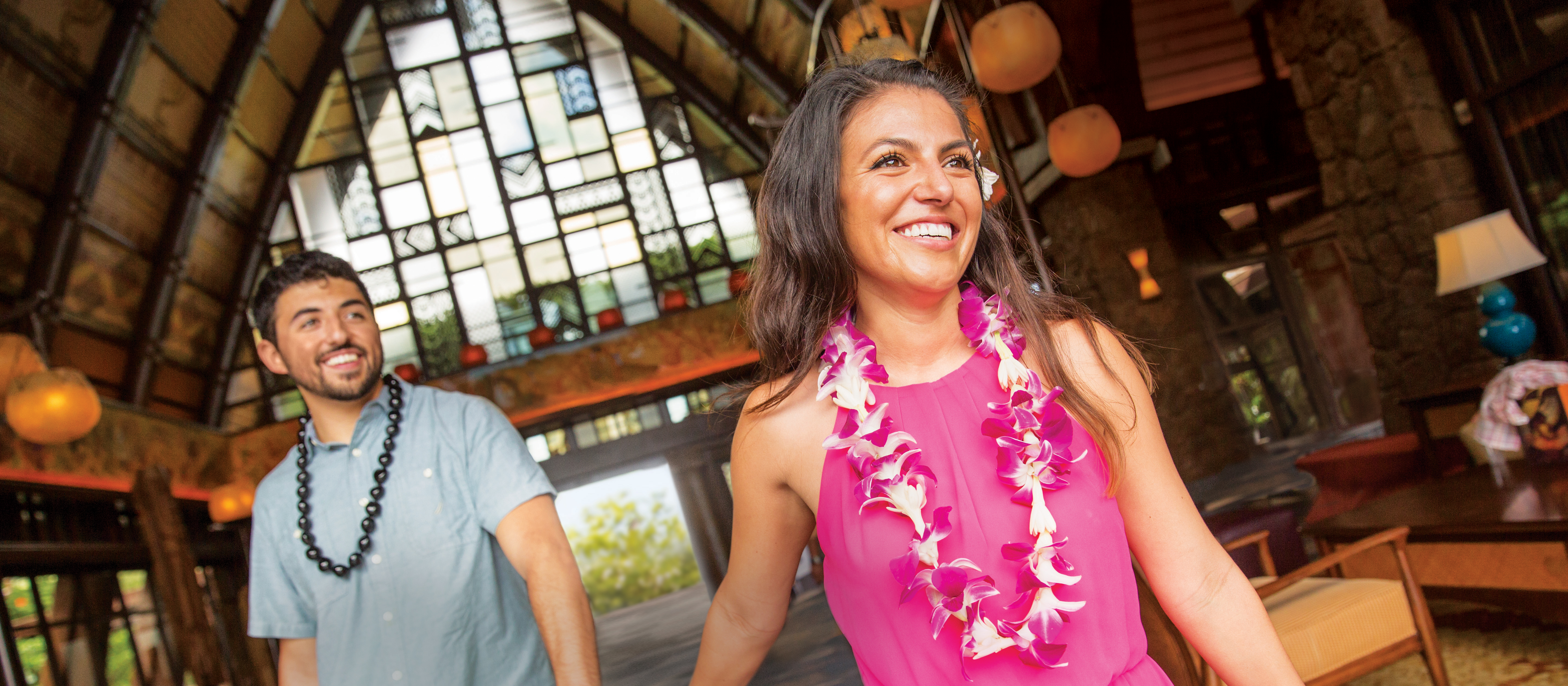 A woman wearing a Hawaiian flower lei holds hands with a man with a Kukui nut lei as they walk through the lobby of Aulani Resort