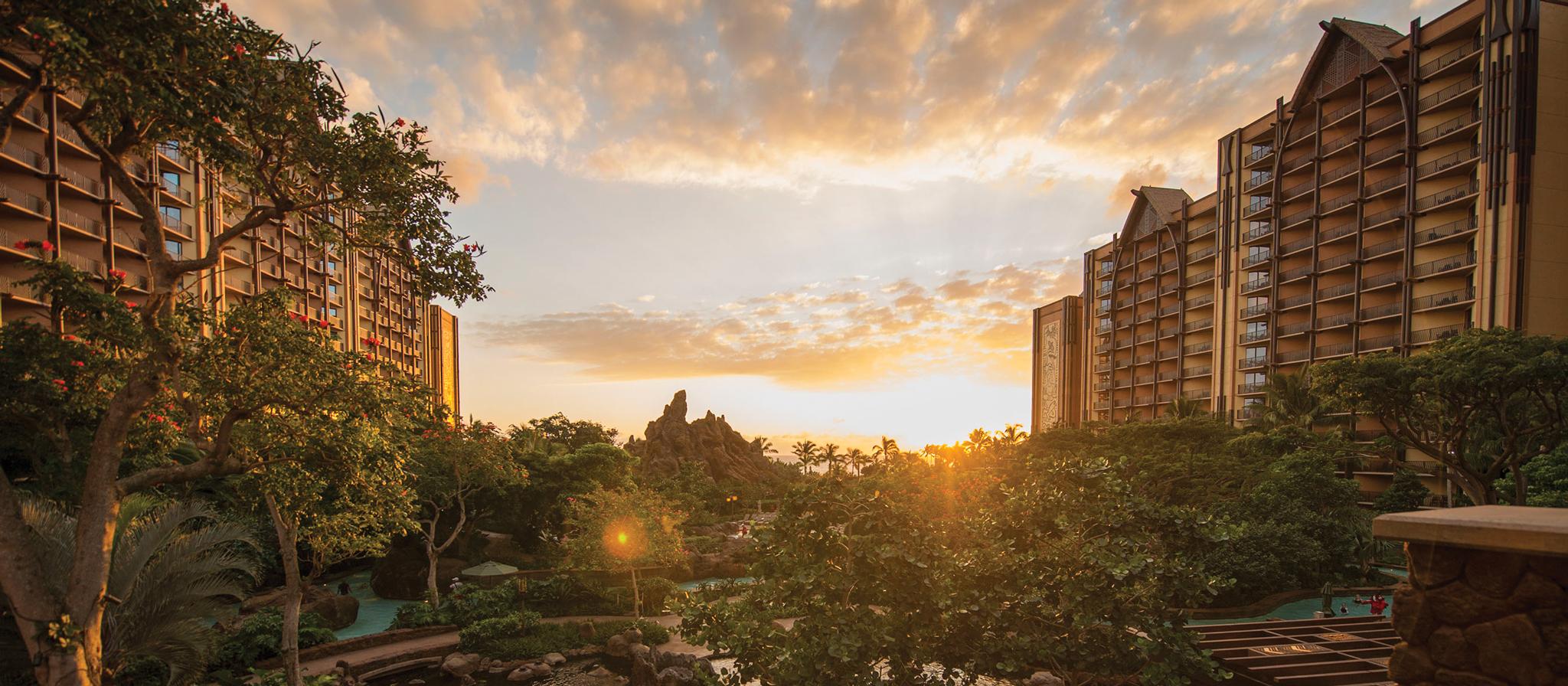 地平線が夕日に輝く曇り空とアウラニのプールエリア