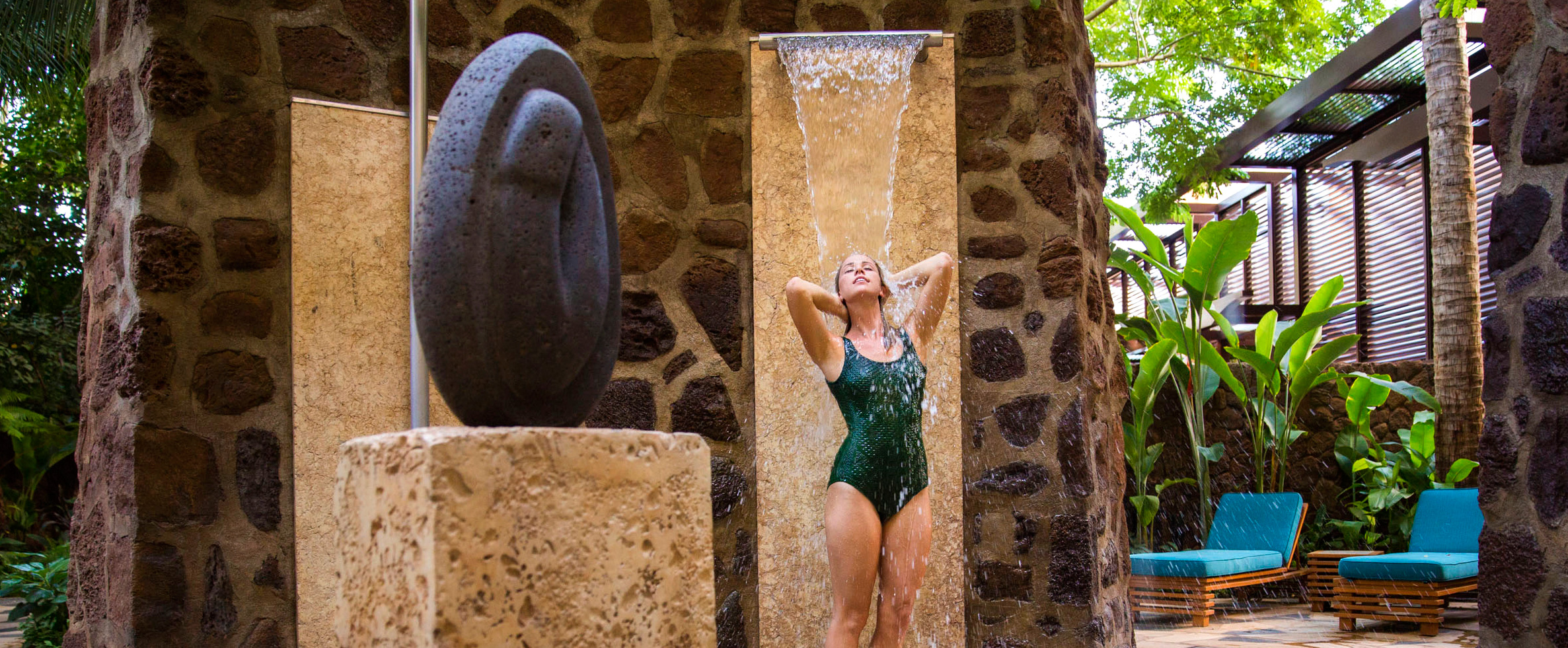 A swimsuited woman bathes under a spray of water at Kula Wai hydrotherapy garden inside Laniwai Spa