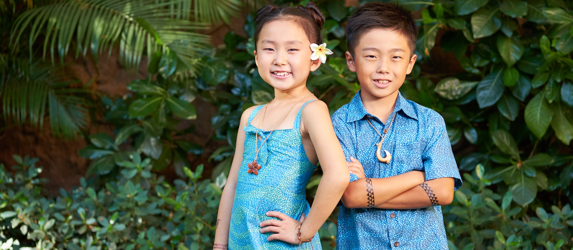 A young boy with temporary tattoos on his crossed arms and a fish hook necklace stands next to a girl with a flower behind her ear