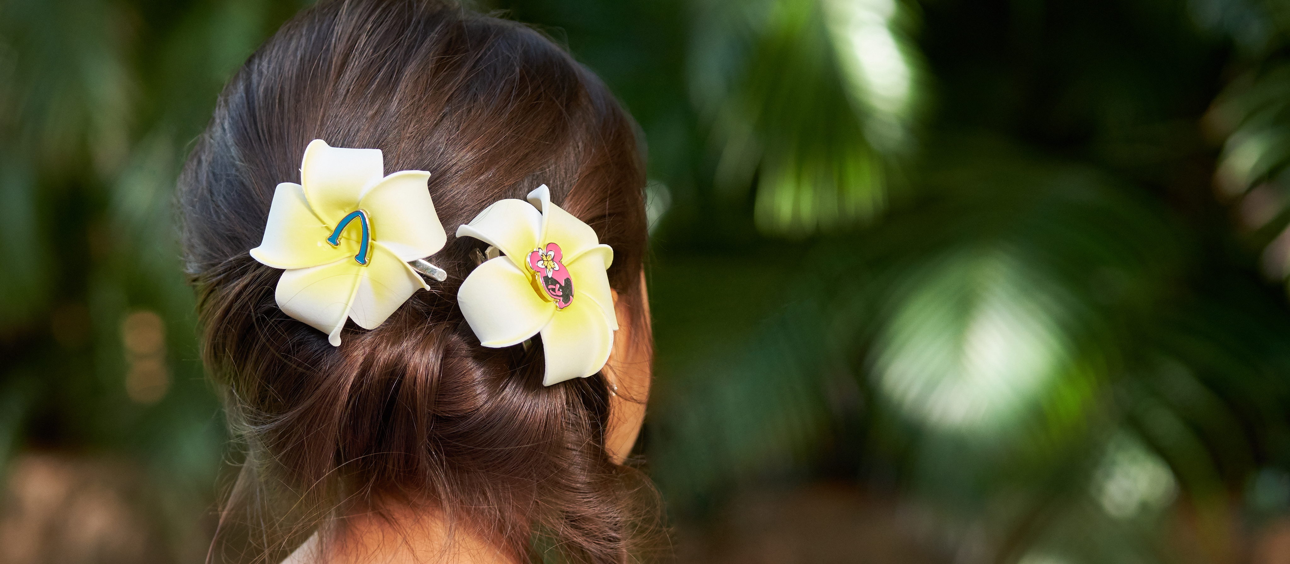 Two Aulani-themed flower clips worn on the back of a young girl's hair