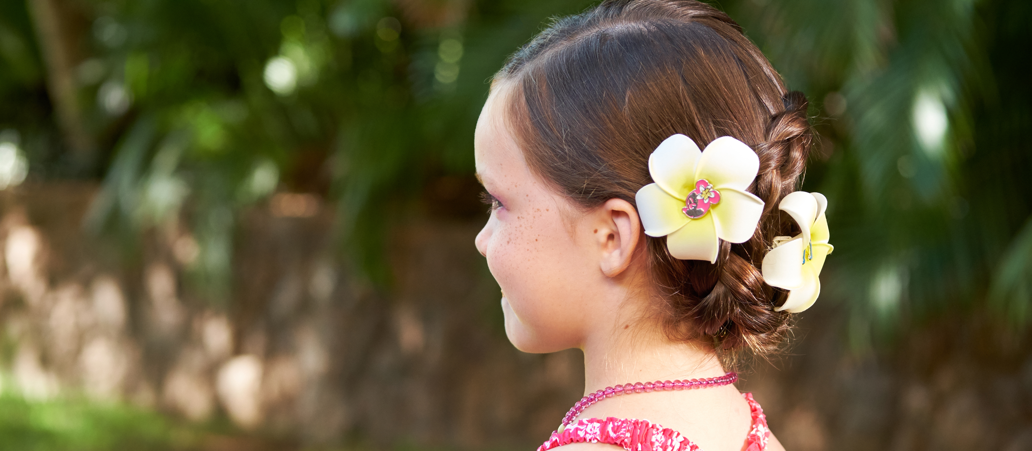 A ¾ profile of a young girl's head with flower clips on the back of her hair.