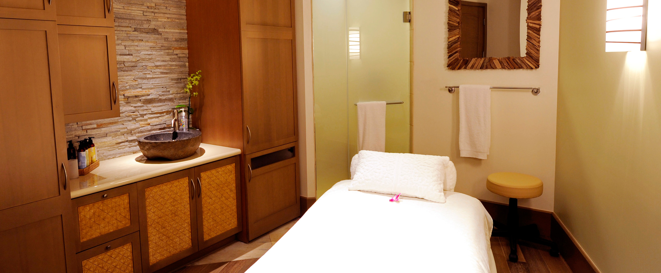 Superieur ... A Massage Table In A Room With Natural Wood Cabinets, A Stone Bowl Sink  And ...