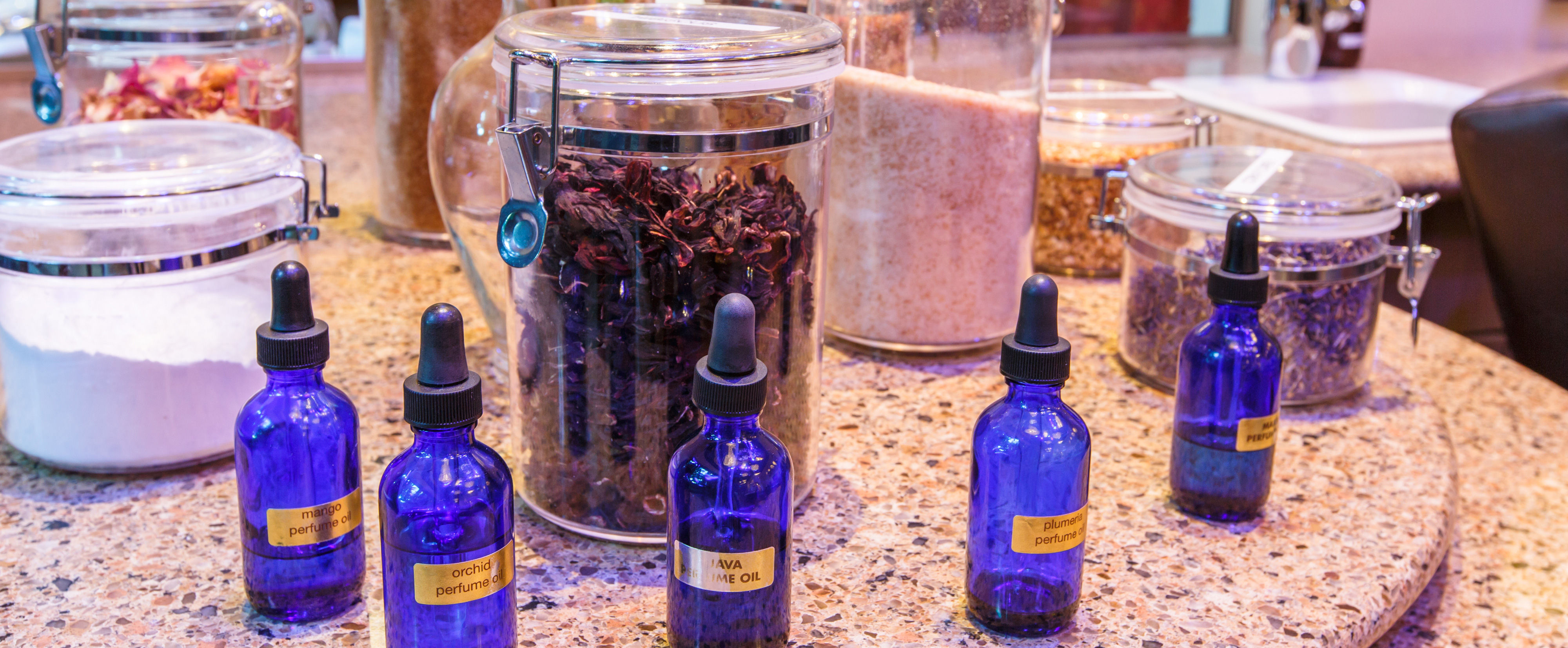 Cobalt dropper bottles filled with essential oils on a granite counter with canisters of dry ingredients