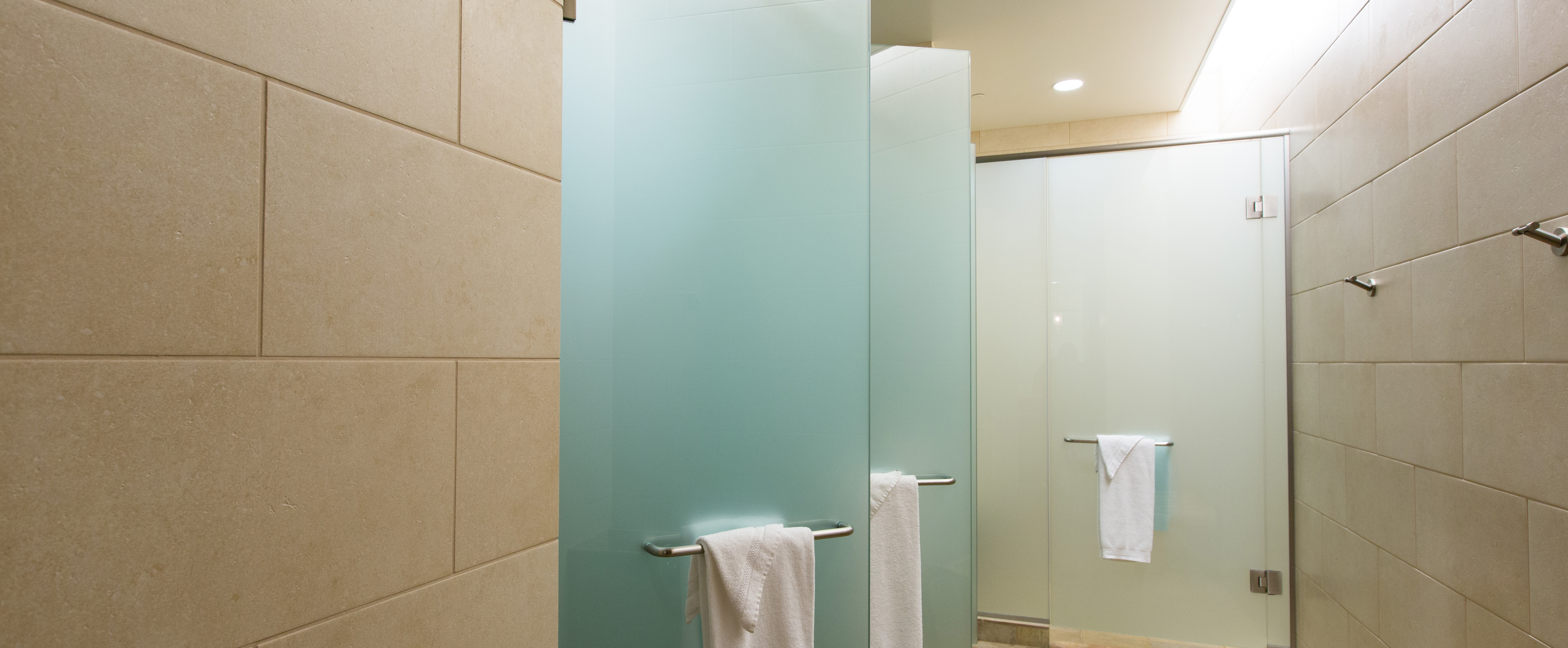 Several showers with frosted-glass doors in a tiled changing room