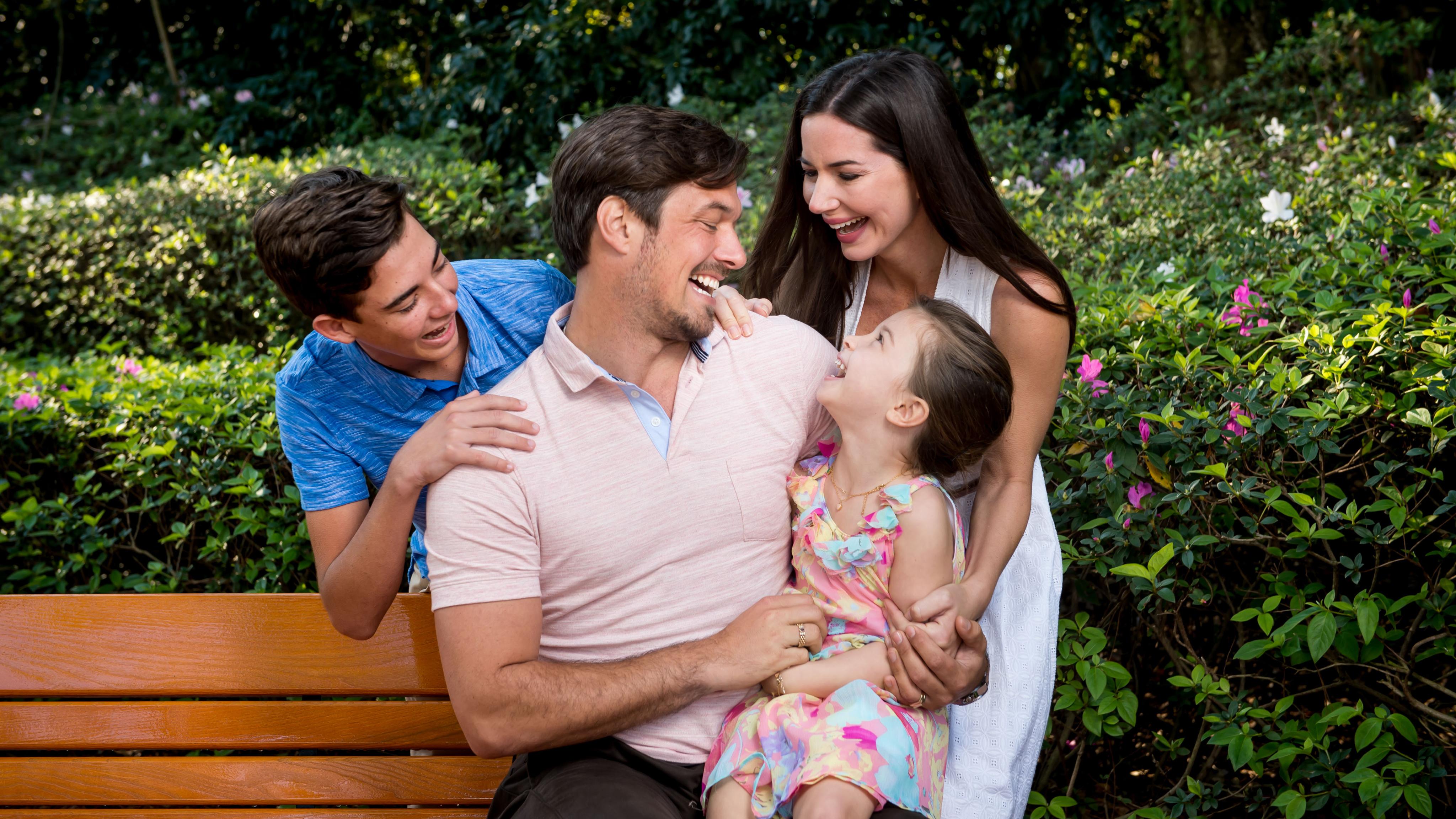 Uma menina sentada no colo do pai com a mãe e o irmão em pé ao lado de um banco, com árvores ao redor