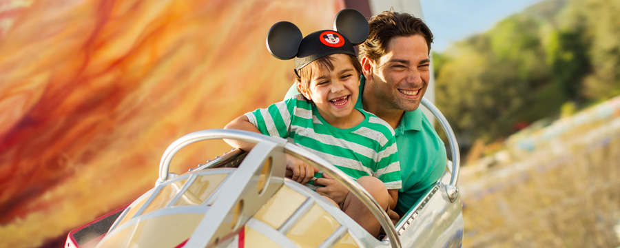 A father and son smile while riding Astro Orbiter in Tomorrowland at Magic Kingdom park