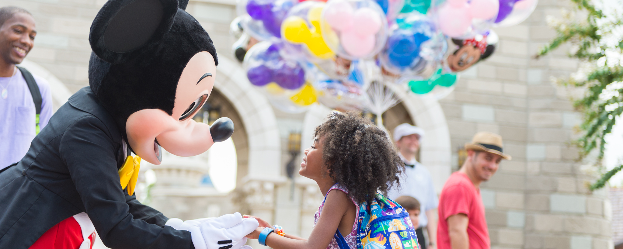 Mickey Mouse greets a smiling young girl in front of Magic Kingdom park