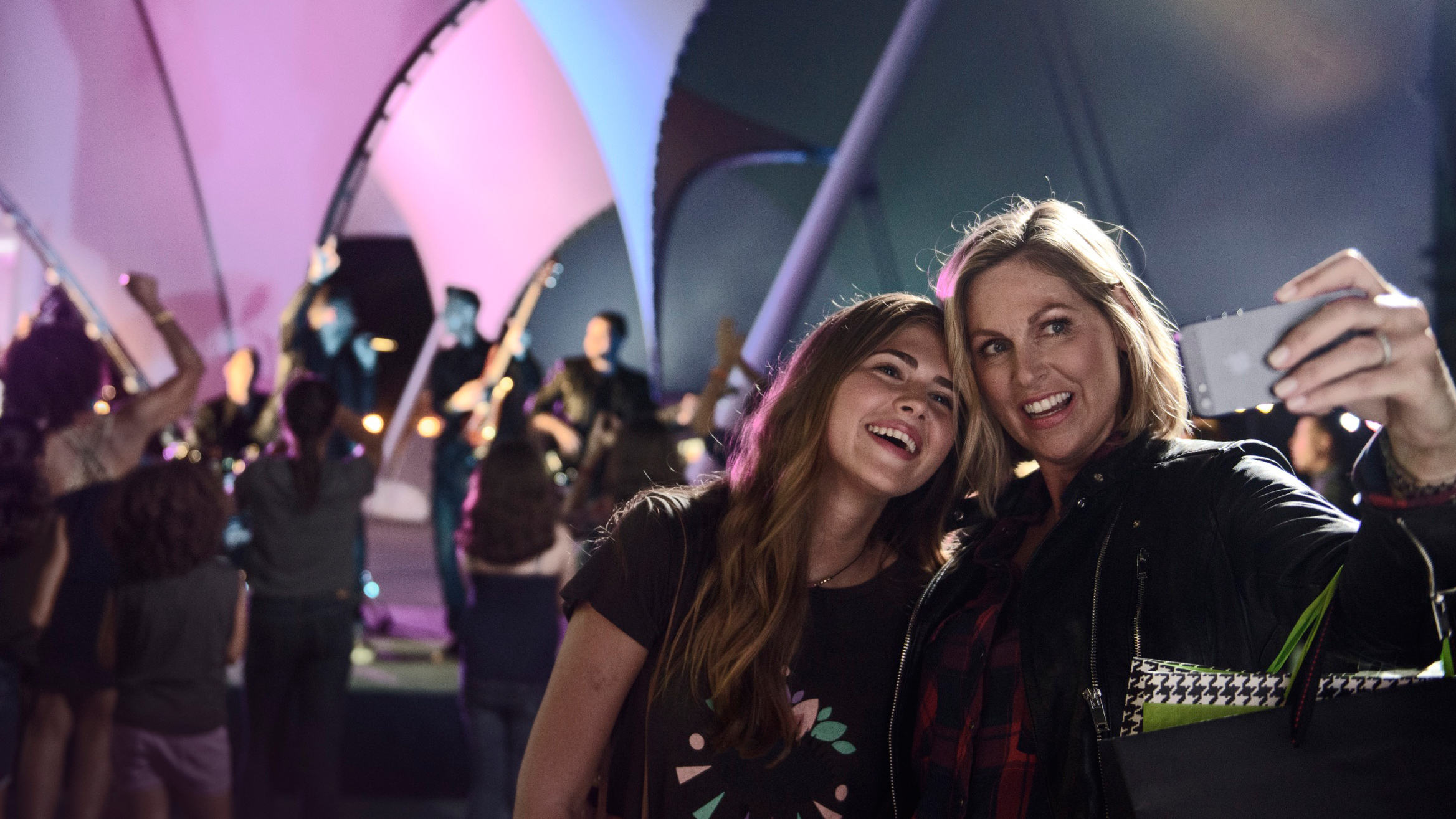 A mother and daughter take a selfie while enjoying an outdoor concert at Disney Springs